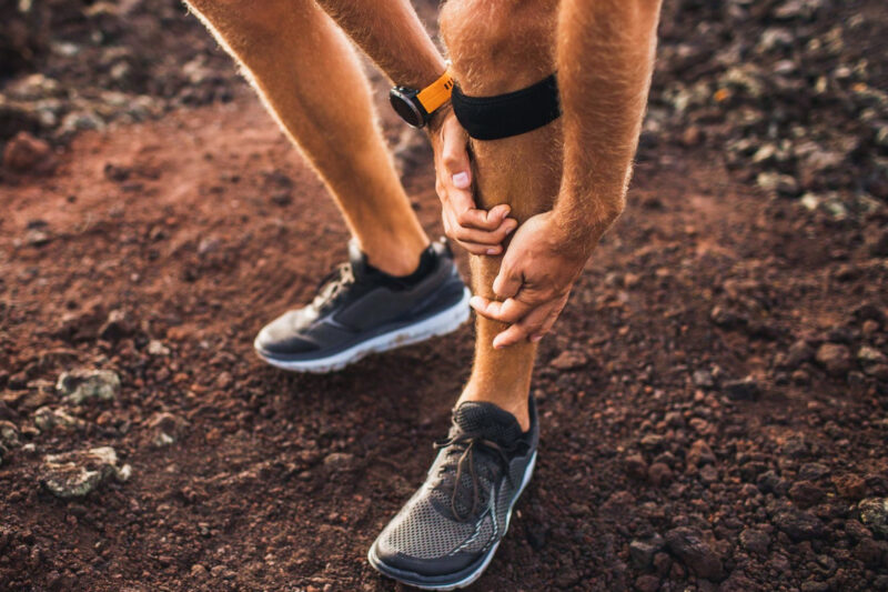 Male runner holding shin in pain due to shin splints