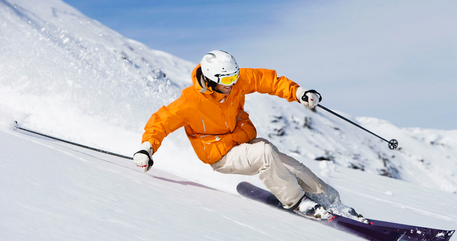 man skiing downhill in orange jacket