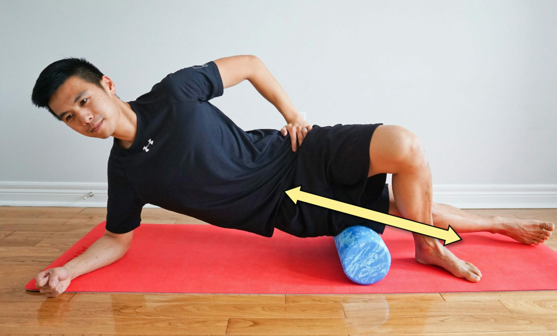 man streching his IT band while side-lying on a roller