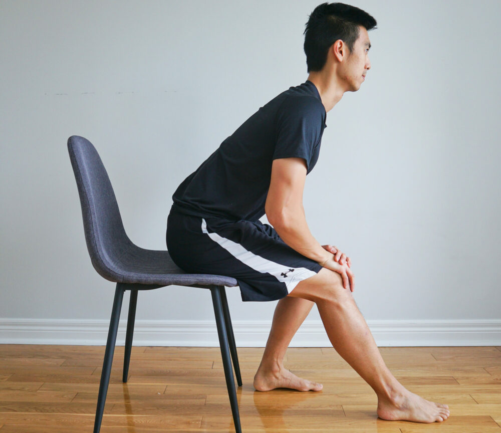 Man stretching his hamstring sitting in a chair