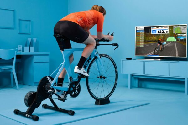 Indoor cycling on a trainer using an workout app on tv screen