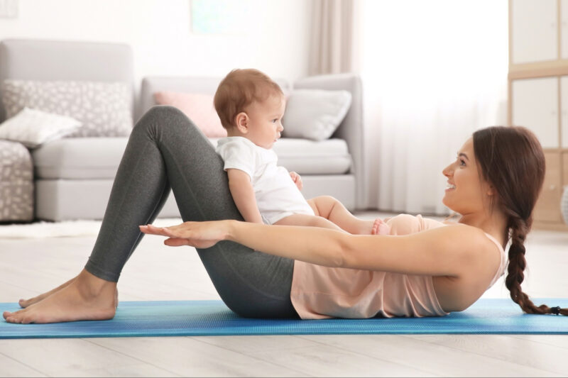 post partum woman exercising with her baby