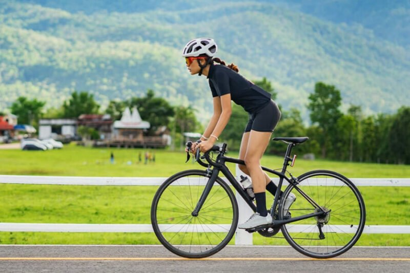 woman cycling on bicycle on country road